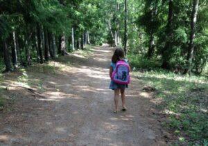 Tyttö kävelee metsätietä koulureppu selässään.
