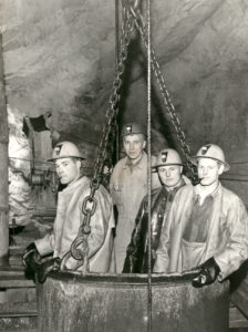 Neljä kaivosmiestä seisoo kaivoksen sisältä otetussa kuvassa kuupassa: kattilamaisessa tynnyrissä, joka roikkuu kettingeillä katosta. Kaivosmiehillä on päässään kypärät ja päällä suoja-asut. Kaksi kaivosmiestä polttaa piippua.