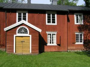 Johannes Lohilammen museon punamullattu kaksikerroksinen päärakennus. Näkyvillä on porstua, jonne johtaa keltamullalla maalattu ovi. Oven yläpuolella on kaari-ikkuna.