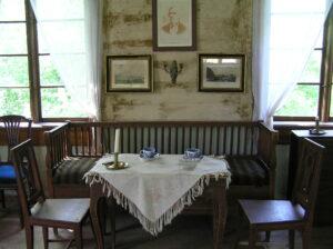 Näkymä Johannes Lohilammen museon yläkerran salista. Kahden ikkunan välissä on pinnasohva, jonka edessä pöytäryhmä tuoleineen. Pöydälle on katettu sinivalkoiset posliinikahvikupit ja kynttilä messinkisessä kynttilänjalassa. Pöydällä on valkoinen, reunoilta hapsutettu liina. Seinällä sohvan yläpuolella on kolme taulua, joista ylin on Elias Lönnrotin kuva. Sen alapuolella on kynttilälampetti.