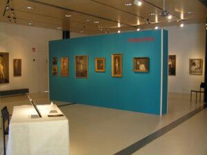 Näkymä Linderinsalin taulunäyttelyyn. Petrolinsiniseen väliseinään on kiinnitetty kuusi ihmishahmoja kuvaavaa maalausta. Salin valkoisilla takaseinillä muita maalauksia.