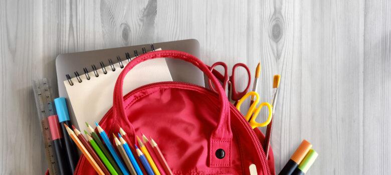 koulureppu täynnä koulutarvikkeita