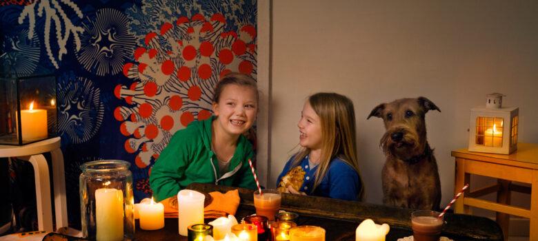 kaksi lasta ja koira kynttilöiden ympäröimänä