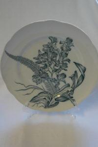 valkoinen ruokalautanen, jossa siniharmahtava kasviaiheinen koristelu