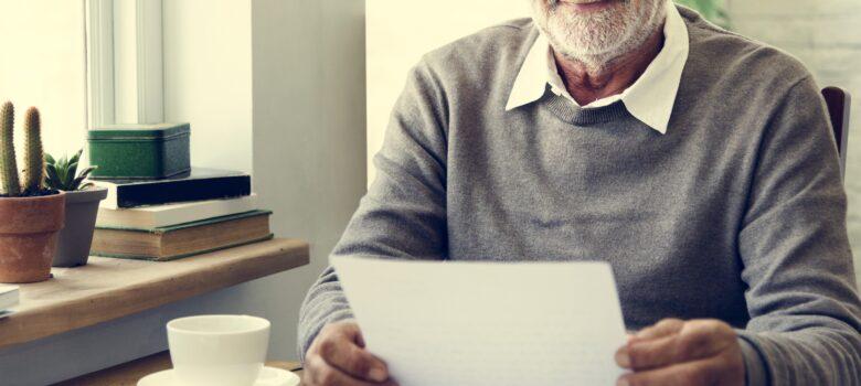 vanha mies lukee kirjettä kahvilassa