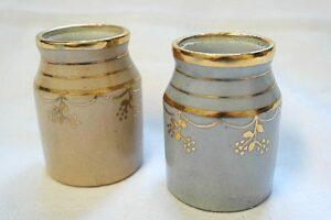 Kaksi pientä purkkia, joissa kultaraitakoristeet.