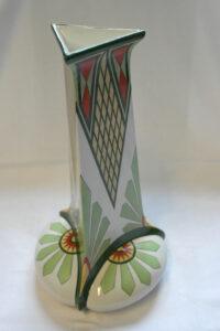 Kolmisivuinen maljakko, jossa valkealla pohjalla vihreän, punaisen ja keltaisen eri sävyillä tehtyä koristelua. Graafista koristelua ja tyyliteltyä kukkakoristelua jalustassa.