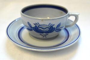 Harmaa kahvikuppi ja aluslautanen, jossa siniset koristelut: lautasessa siniset laidat, kupissa tyylitelty kukkakoriste.
