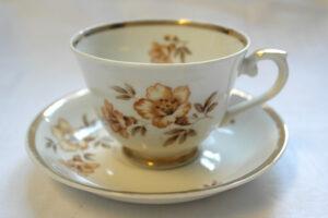 Valkoinen posliinikuppipari. Kupissa ja lautasessa kultareunus ja keltaruskea kukkakuvio.