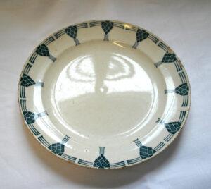 Valkoinen ruokalautanen, jonka yläreunaa kiertää sininen käpy-ornamenttikuvio