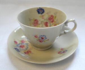 Valkoinen kahvikuppipari, jossa värikkäitä kukkakuvioita.