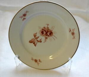 Valkoinen lautanen, jossa kultareunus ja ruskeita kukkakoristeita.