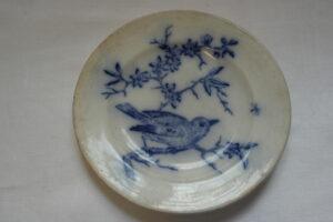 valkoinen aluslautanen, jossa sininen lintu ja oksa -koriste