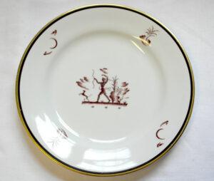 Valkoinen lautanen jossa kultareunus ja reunaa kiertävä ruskea raita. Keskellä varjokuvan tyylinen sivusta kuvattu metsästäjähahmo jousipyssyn ja koiran kanssa. Keskuskuvassa on myös kasvillisuutta.