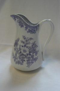 Valkoinen kannu sinisillä kasviaiheisilla koristeilla.