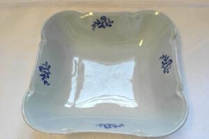 Neliön muotoinen valkoinen matala kulho, jonka nurkat ovat pyöristetyt. Jokaisella sivulla sininen kukkakuvio.