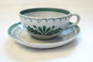 Valko-vihreä kuppi ja aluslautanen. Kupin kyljessä on tyylitelty kukka-koristekuvio.