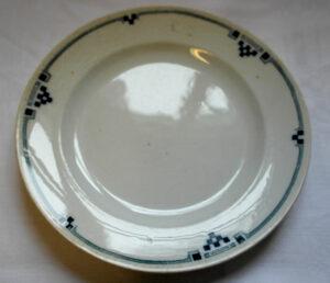 valkoinen lautanen, jonka reunaa kiertää sininen graafinen nauhakuvio.
