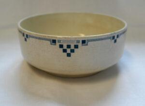 Valkoinen kulho, jonka yläreunaa kiertää sininen graafinen nauha-ornamenttikuvio.