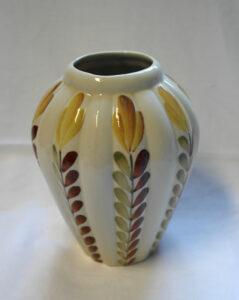 Maljakko, jossa ruskeasävyinen tyylitelty, käsinmaalattu kukkakuviointi.