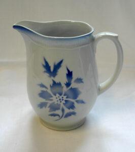 Vaalea kannu, jonka kyljessä on sininen kukkakoriste.