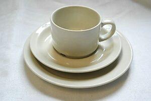 Valkoinen kahvikuppi,  jonka alla on aluslautanen ja pullalautanen.