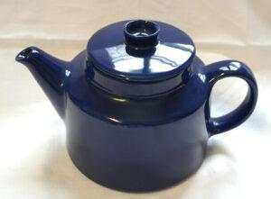 Tummansininen teekannu.