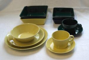 Keltaisia ja vihreitä astioita: lautasia, kulhoja ja kuppeja.