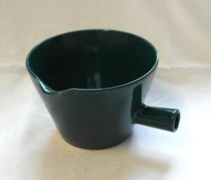 Vihreä kulho, jossa on kädensija ja kaatonokka.
