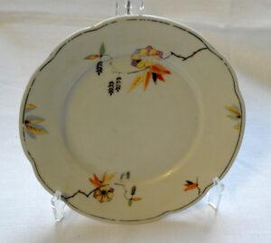 Valkoinen posliinilautanen, jonka ulkoreunassa on kultaraita. Lautasta koristaa monivärinen koivunurpu-koriste.