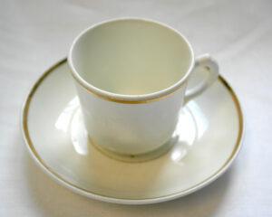 Valkoinen kuppipari. Kupin ja lautasen reunaa kiertää kultaraita.