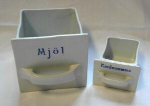 Kaksi kahvalla varustettua posliinista laatikkoa, jotka kuuluvat keittiölokerikkoon. Valkoisten lokerikkojen kyljessä siniset tekstit: Mjöl ja Kardemumma.