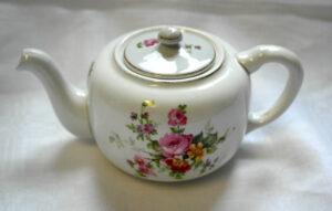 Pieni valkoinen teekannu, jossa värikkäät kukkakoristeet kyljessä ja kannessa.