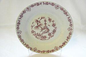 Ruokalautanen, jossa viininpunaisia itämaishenkisiä koristeita lautasen keskellä ja reunassa.