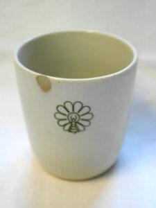 Valkoinen muki, jossa ei ole korvaa. Mukin kyljessä on tyylitelty vihreä kuvio, jossa yhdistyy päivänkakkara ja mehiläinen.