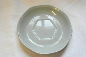 Vaaleanharmaa aluslautanen kupille, jossa keskellä kuusikulmion mallinen kupinsyvennys.