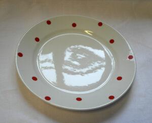 Valkoinen lautanen, jossa on punaisia pilkkuja.