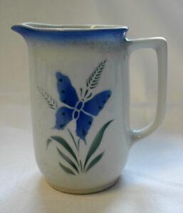 Valkoinen kannu, jossa sininen perhonen ja yläreuna sekä vihreää heinäkuviota.