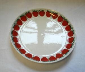 Valkoinen aluslautanen, jonka reunaa kiertää rivi punaisia mansikoita.