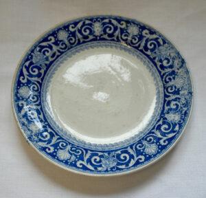 Sini-valkoinen aluslautanen. Sininen koristekuvio kiertää lautasen reunaa.