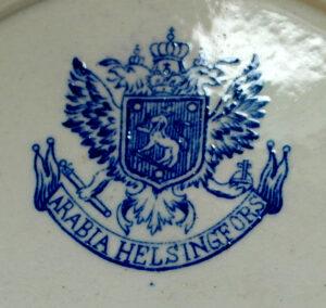 Arabia -astiatehtaan leima, joka kertoo, että kyseinen esine on valmistettu vuosina 1878-1910 Leimassa on kaksipäinen kotka , keskellä vaakuna ja alaosassa teksti ARABIA HELSINGFORS
