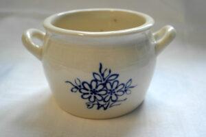 Vaalea posliiniruukku, jonka sivuilla kahvat. Kyljessä sininen kukka-aiheinen koristelu.