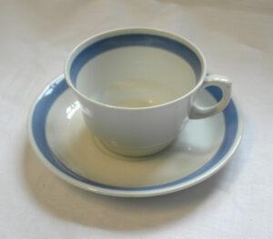 Valkoinen kuppipari. Kupin ja aluslautasen reunaa kiertää leveä sininen raita.