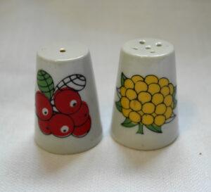 Pienet sormustimenmuotoiset suola- ja pippurisirottimet. Toisen sirottimen kyljessä puolukka-koriste, toisen kyljessä lakka-koriste.
