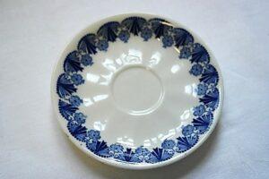 Kahvikupin aluslautanen. Valkopohjainen lautanen, reunaa kiertää sininen kukka-aiheinen koristelu.