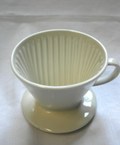 Valkoinen posliininen suodatinsuppilo kahville.