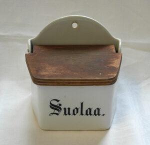 Valkoinen suola-astia, jossa puinen kansi. Kyljessä musta teksti Suolaa.