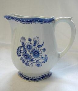 Valkoinen kannu, jossa sininen kukkakoristelu sekä sininen ornamenttikuvio kannun ylä- ja alareunassa.