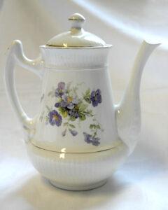 Valkoinen posliininen kahvikannu, jonka kyljessä on orvokkiaiheinen kukkakoriste