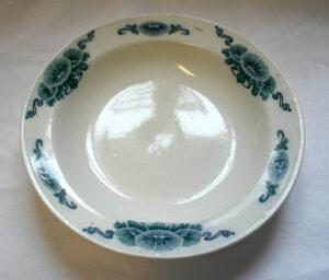 Valkoinen lautanen, jonka yläreunassa on sini-vihertäviä kukka-kuvioita.